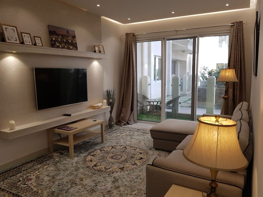 Modern Living area with dinning table for 4 people with sitting area in balcony with garden view