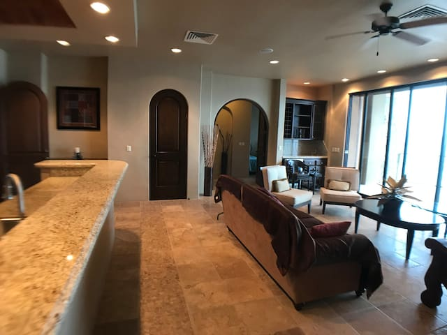Living room area with kitchen to the left, wall of windows to the sea and door to master bedroom suite straight ahead.