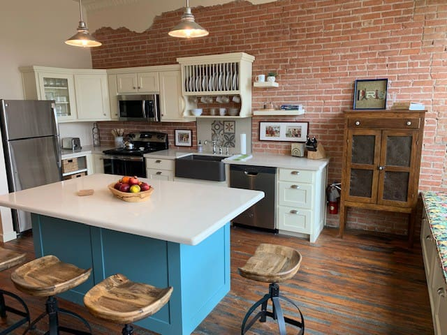 A charming bright kitchen was added to this 1917 historic  building featuring orginal  brick wall,  tin ceilings and pine floors.