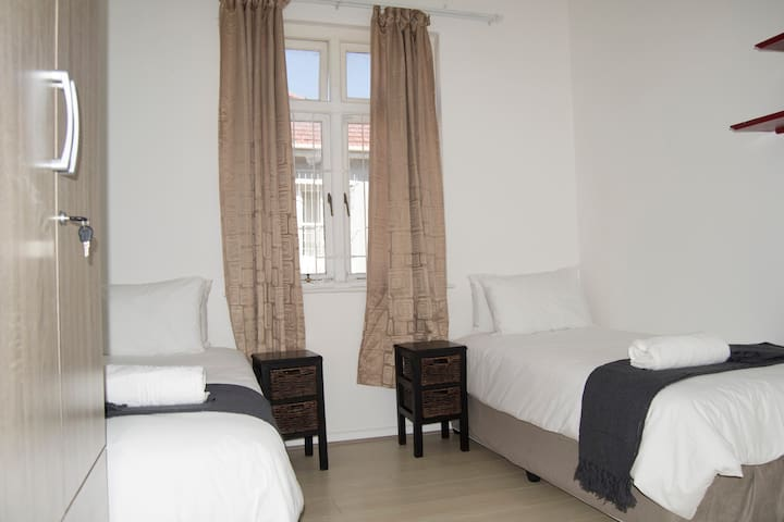 1st Bedroom consisting of x2 single beds and ample wardrobe space with laminated flooring.