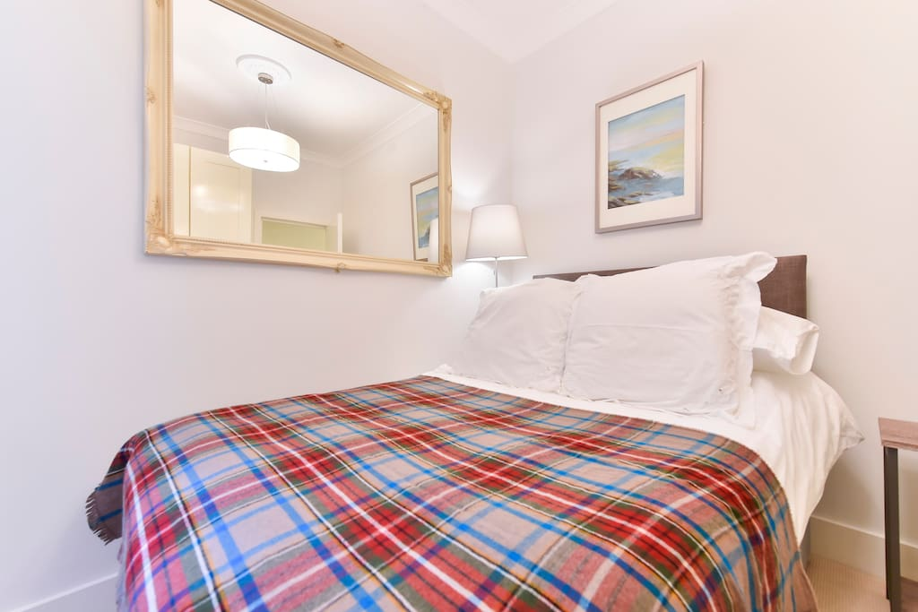 The comfortable master bedroom has a cosy double bed, French windows letting in plenty of light, lots of cupboard storage space and a mirror. Linen and towels are provided.