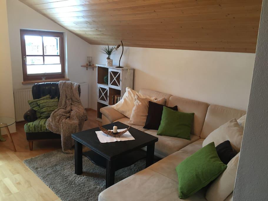 Wohnzimmer mit großer gemütlicher Couch und Chefsessel