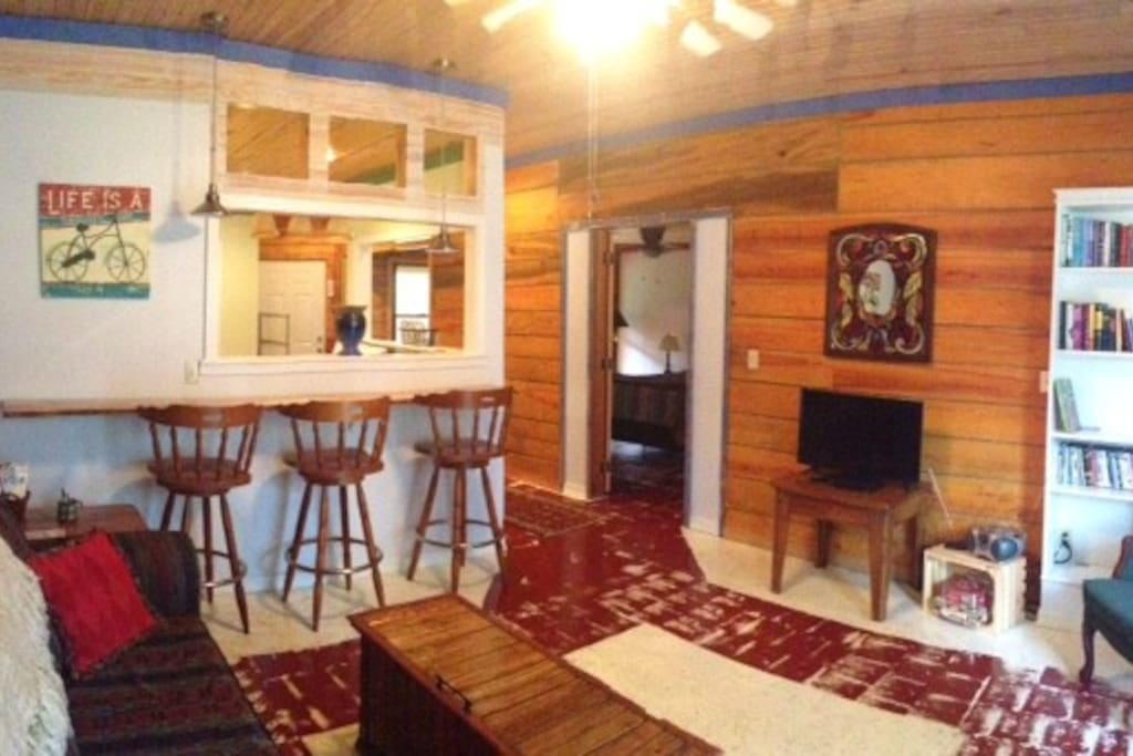 Nice open-flow space with rough sawn lumber walls, pine-top bar, reading corner, and sofa sleeper.