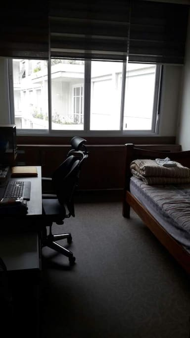 Quarto 1 - com mesa e cadeira de escritório, cama de solteiro, prateleira para livros, guarda roupas, televisão.