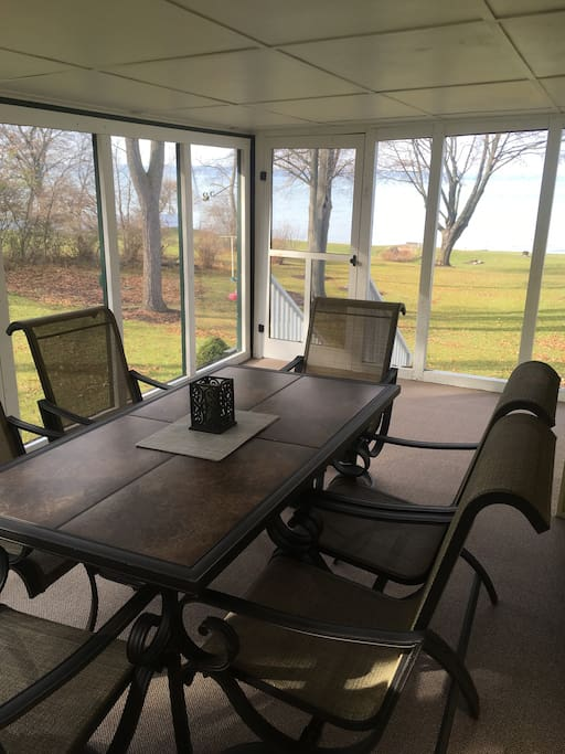 Screened in porch with table and seating for 6 over looking the lake. A guest favorite!