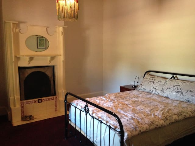 Main bedroom with queen bed and fire place.