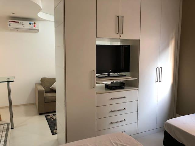 Vista do dormitório com TV por assinatura, ar condicionado split e cortina black-out.