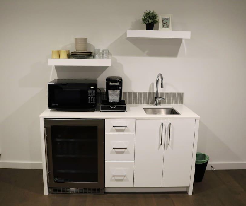 Modern Kitchenette with mini fridge, coffee maker, hot plate, utensils, and other basics