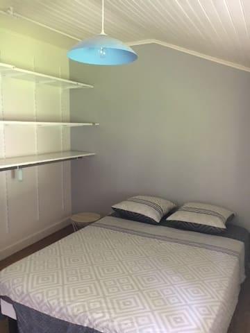chambre avec un lit double et dressing ouvert sol en parquet bois massif