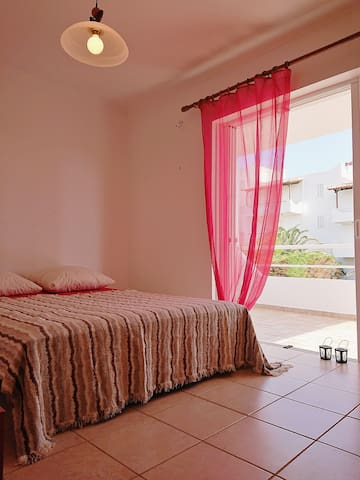 Master bedroom with double bed, window door and private balcony.  Large closet wall with drawers and shelves.