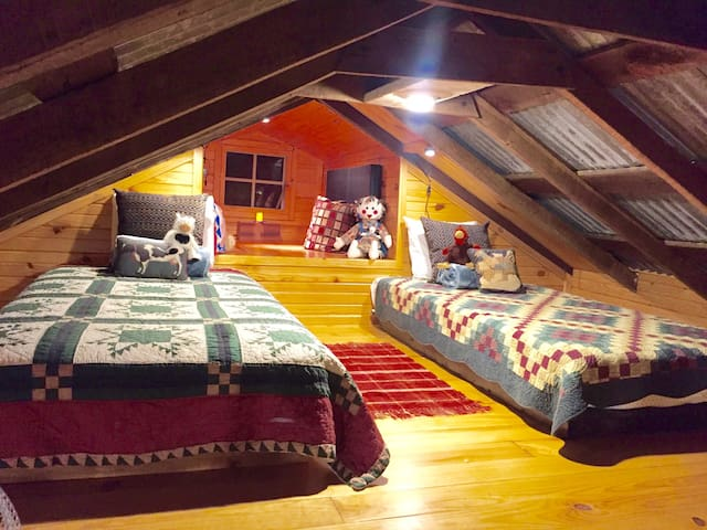 Sleeping loft has two single beds and a reading dormer overlooking the creek.