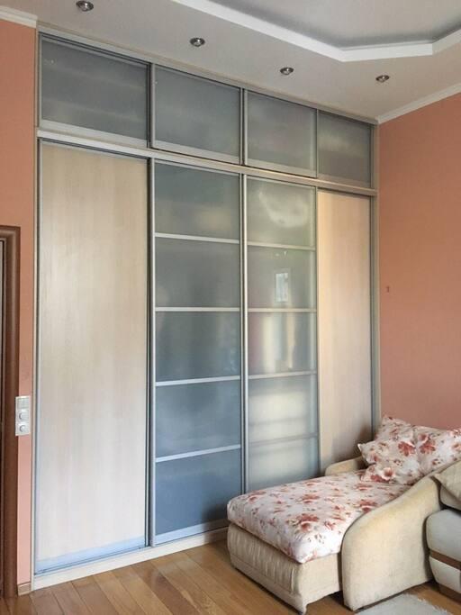 Bedroom-1 (studio couch, single bed, piano, bookshelves, TV, large wardrobe)