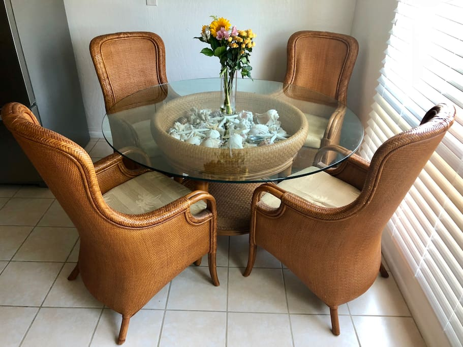 Beautiful Tommy Bahama dining table with seashells inside and fresh flowers every week!