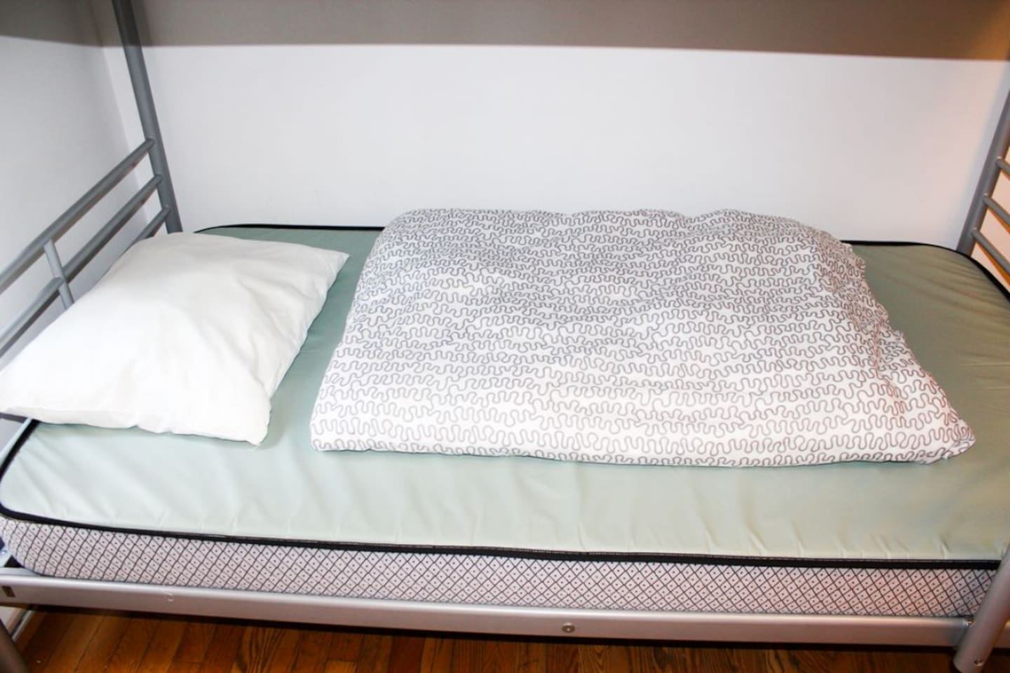 Closeup of a bed, notice they are covered with vinyl for hygiene.
