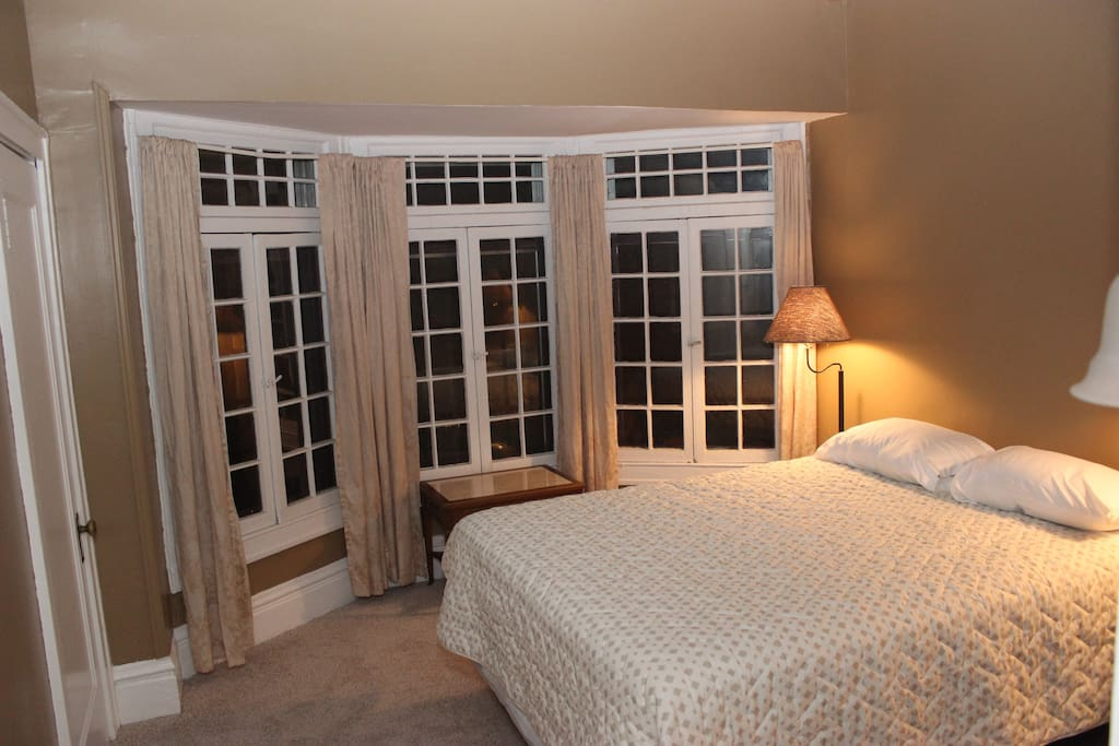 The bedroom has a large bay of french casement windows and a queen-size bed.