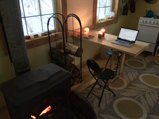 A woodstove burning cozily, a fold-down table/desk, and plenty of views of the forest in every direction!
