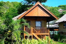 The delightful sea view bungalow is surrounded by tropical gardens