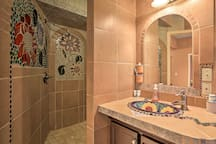 The master bath features a unique open walk-in shower with mosaic wall decor.
