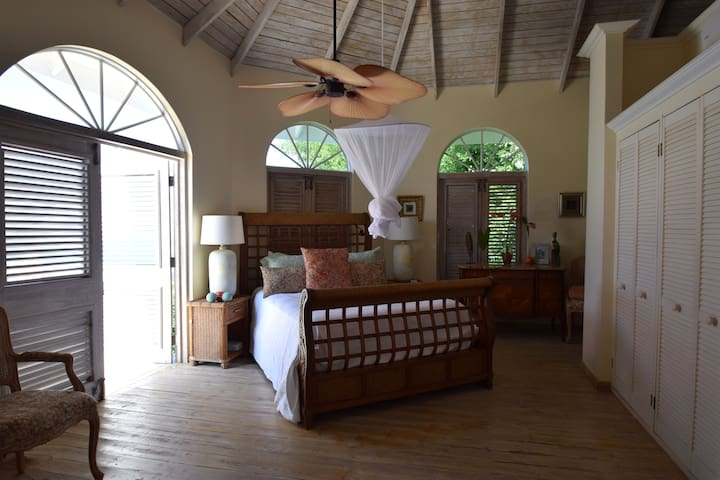 Queen-sized sleigh bed in guest bedroom, with double doors and view of Pitons