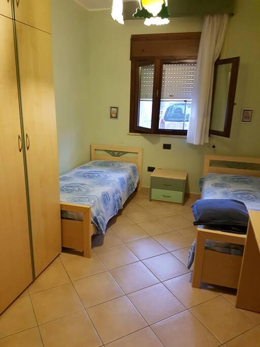 Camera con due lettini armadio e scrivania