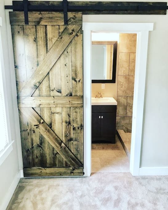 Custom real wood sliding barn door to ensuite master bathroom