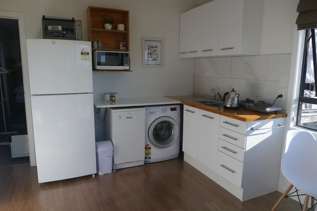Newly renovated kitchen with dishwasher, washing machine, large fridge/freezer, bench top cooking facilities and microwave oven