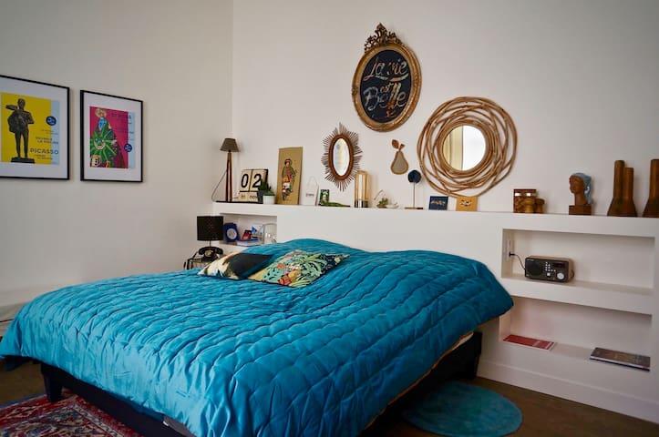 Chambre avec deux grandes fenêtre avec persiennes