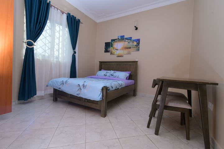 Large, well lit and aerated bedroom area with double bed and dedicated work space for 2