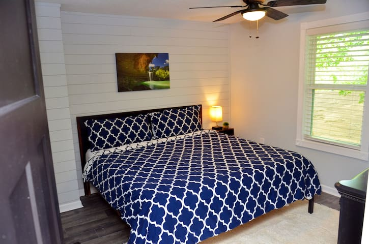 This first bedroom features a king sized bed, dresser, and night stand with USB and power plugs