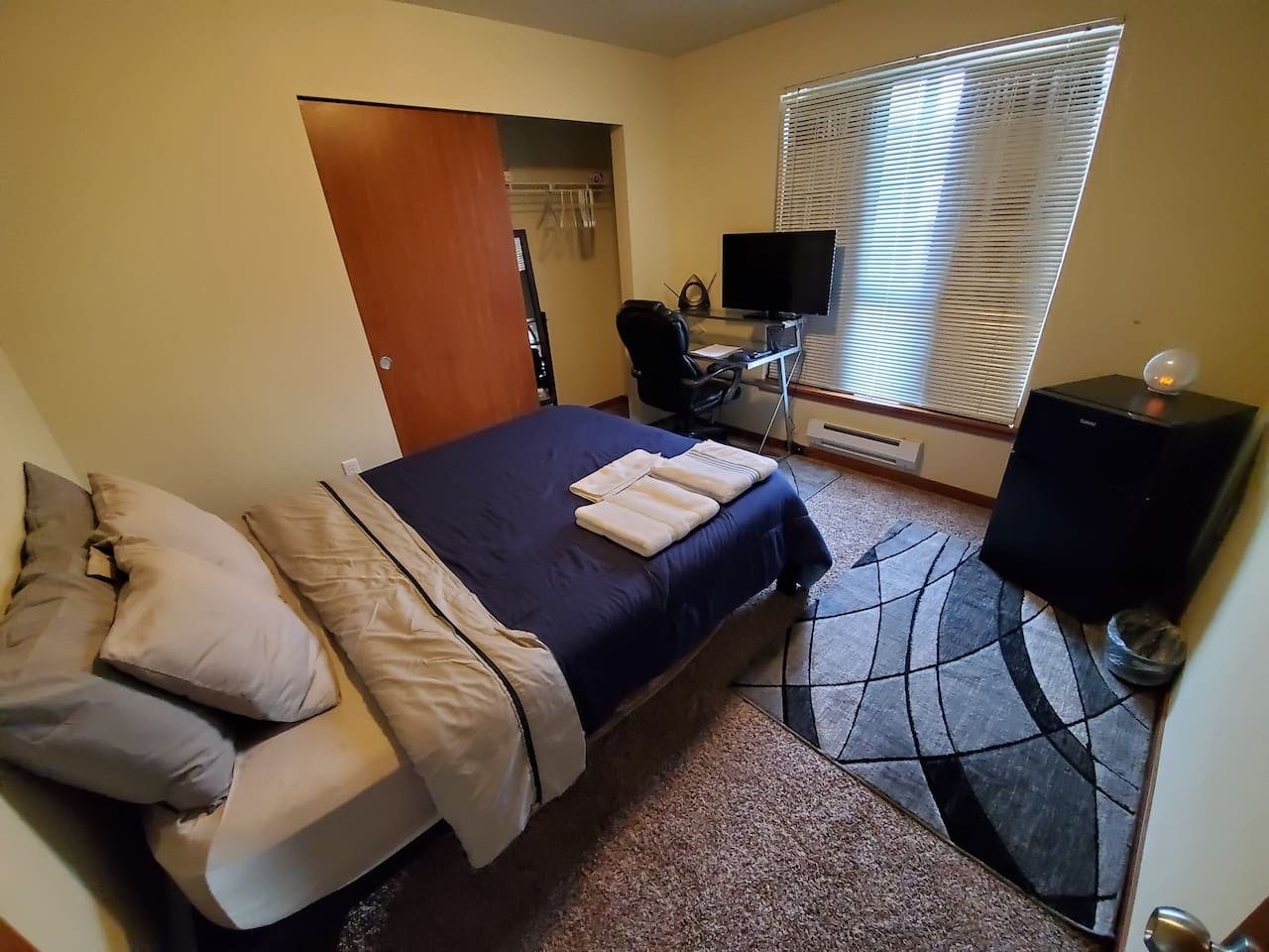 Bedroom with Queen Mattress, Mirror, TV, Laptop Friendly Workspace and Mini Refrigerator with Freezer.