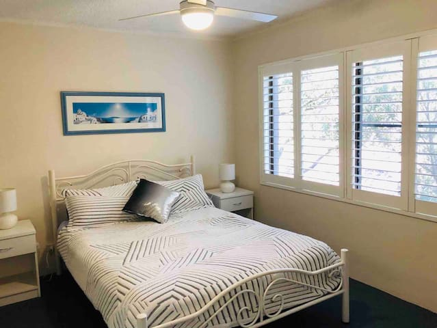 Main bedroom with walk in wardrobe and ceiling fan.