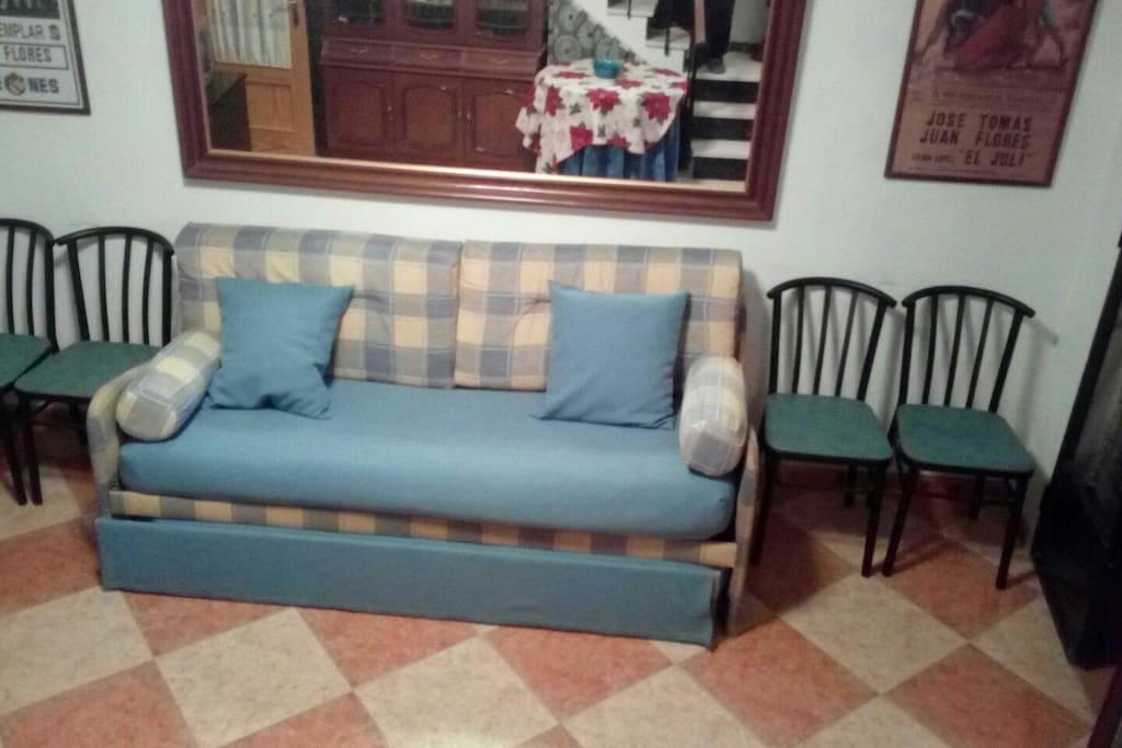 justo al entrar a la casa hay un ancho pasillo y una segunda puerta de seguridad que al abrirla das con este gran salon y con este sofa que se convierte en dos camas.Véase siguiente foto