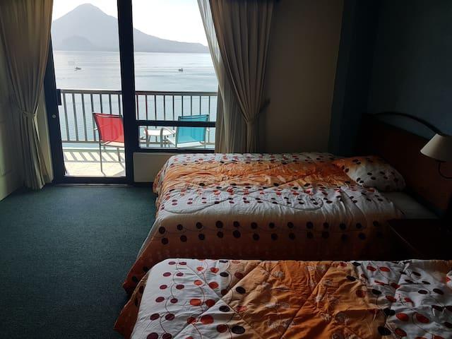 Dormitorio 2 con 1 cama queen y 1 individual y 1 colchon individual con vista al lago