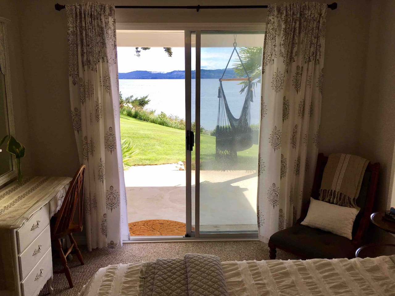 Bright ocean view bedroom with sliding doors leading to private patio.