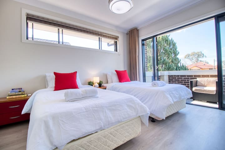 Two king single size bed with sun-filled balcony