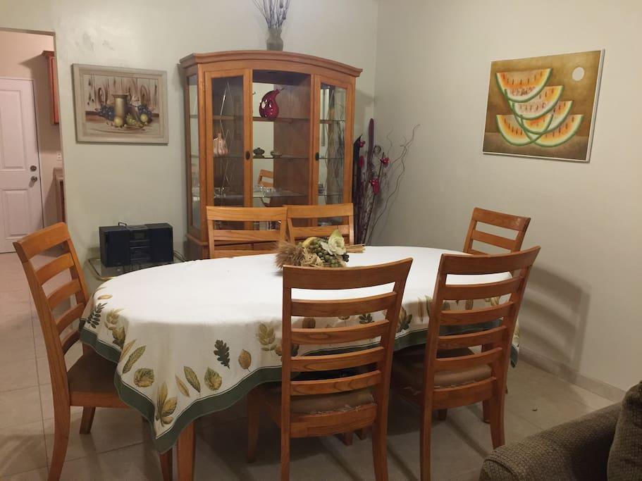 Comedor de de seis sillas, mesa ovalada y vitrina.