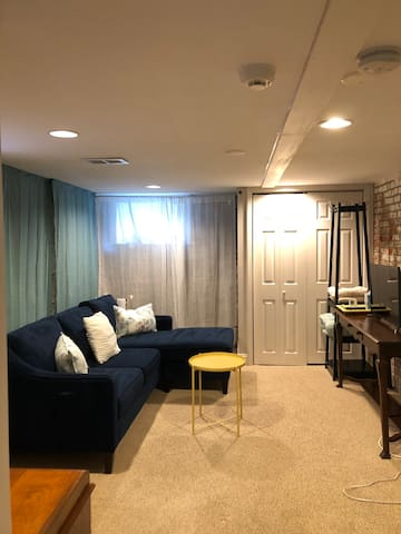 Basement living room with new west elm chaise lounge couch and smart tv