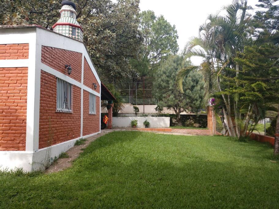 Jardín espacioso al frente de la cabaña dando hacia la calle empedrada Rosa Morada