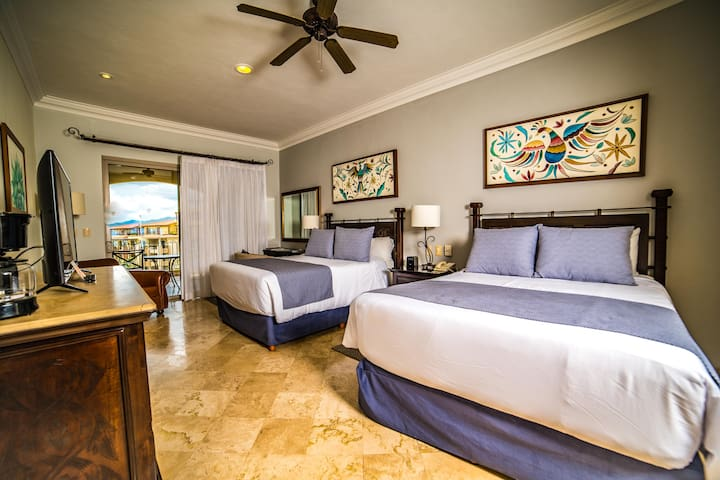 Two queen beds in second bedroom, complete with luxury bedding and ocean views.