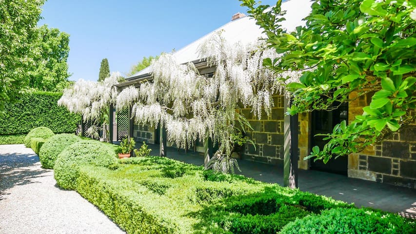 The front verandah in spring, covered with Wisteria Alba. The house features wall of local bluestone.