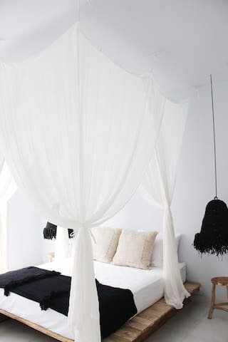 comfortable bed with 4 pillows and a unique mosquito net