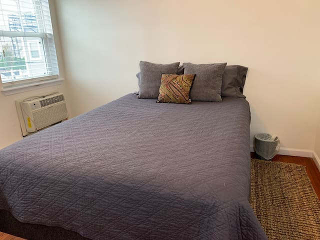 Spacious windowed bedroom with Queen size bed with Sleeprest mattress. 400 thread-count linens provide for a comfortable sheet. Safavieh runner adds warmth to the rich-colored hardwood floors.. Air conditioning unit keeps bedroom cool in summertime.