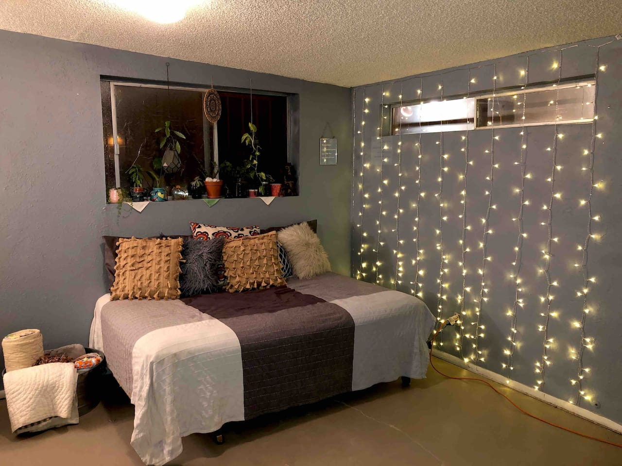 full size mattress bed with extra bedding in bucket • dangly lights & houseplants area