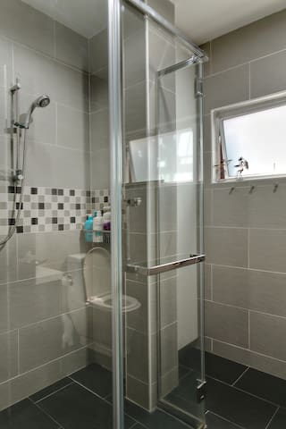 Downstairs Bathroom: Shower in a clean, modern bathroom, equipped with warm water.