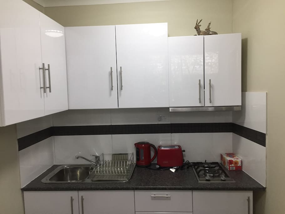 Kitchen with appliances, cooktop, fridge, microwave, cutlery, bowls, plates, pots and pans. Also includes oil, sugar, tea, salt and pepper.