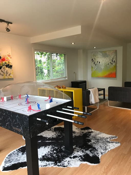 Games room with two couches, fireplace, bubble hockey table and board games (small selection of children's toys)