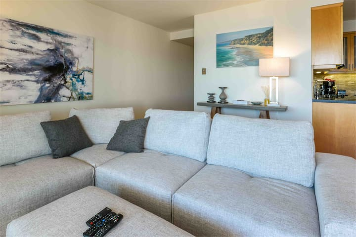 Living room with couch that converts into extra deep seating, large smart TV with cable and apps and view onto private patio overlooking Malibu beach