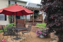 Patio with umbrella table and seating for four guests.