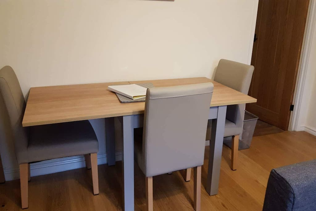 The dining table in the living room seats up to five people when extended (as shown) or up to three people when not extended.