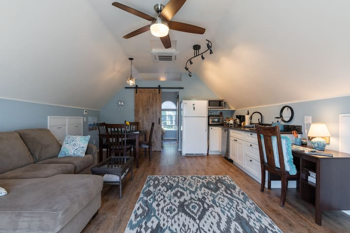 Inside is an open floor plan with a sofa and chair, dining area, and kitchen. A barn door separates the bedroom.